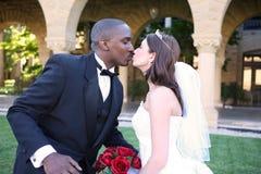 Man and Woman Interracial Wedding Couple Kiss. A young and attractive man and woman wedding couple kissing outside church Stock Photography
