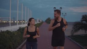 Man and woman joggers are flirting during evening running outdoors, happy faces