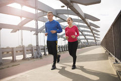 Man and woman jogging on a bridge on a sunny day stock photography