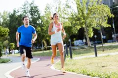 A man and a woman jogging. A men and a women jogging on a city track royalty free stock image