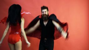 Man and woman jump. Funny couple jumping on a red background. Bearded man in black coat and girl in latex overalls with. Wings having fun and jumping. Red stock footage