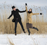 Man and woman jump on lake beach Royalty Free Stock Photo