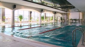 Man and a woman jump into the pool and swim a race. Scene. Young couple of swimmers inside swimming pool.  stock footage