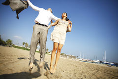 Man and woman jumping on beach Royalty Free Stock Photos