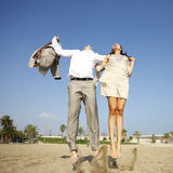 Man and woman jumping on beach Royalty Free Stock Photography