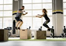 Man and woman jumping on boxes in gym Stock Photo