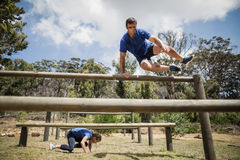 Man and woman jumping over the hurdles during obstacle course. Man and women jumping over the hurdles during obstacle course in boot camp royalty free stock photo