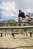 Man and woman jumping over the hurdles during obstacle course Stock Photography
