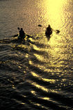 Man and Woman Kayaking at Sunset. Silhouette of Man and Woman Kayaking on a Lake at Sunset Stock Photo