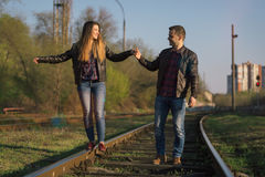 A man and a woman are kept in hand and go by rail. Royalty Free Stock Images