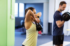 Man and woman with kettlebell exercising in gym. Sport, fitness, lifestyle and people concept - women with kettlebell and men with dumbbell exercising in gym Royalty Free Stock Images