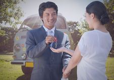 Man and woman with keys in front of camper van Stock Photo