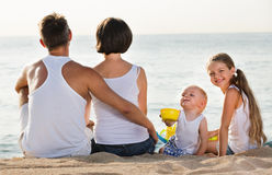 Man and woman with kids sitting with back to camera on  beach. Glad positive men and women with two kids sitting with back to camera on sandy beach Royalty Free Stock Images