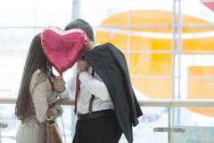 Man and woman kiss behind heart shaped balloon Royalty Free Stock Images