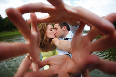 Man and woman kiss reaching their hands out to the camera Royalty Free Stock Photos