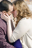 Man and Woman Kissing. A man and woman kissing each other outdoors Stock Image