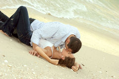 Man and woman kissing on beach in wet clothes Stock Images