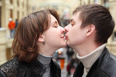 Man and woman kissing on city street. Happy adult man and woman in leather jackets kissing on city street Stock Photos