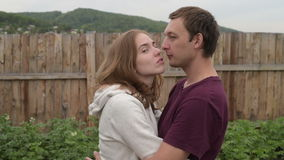 Man and woman kissing and laughing. Both are happy. They are staying outdoors on a summer cloudy day againts a wooden fence background stock video
