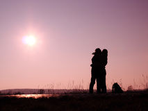 Man and woman kissing. Silhouette of men and women in an embrace and kissing in the sun Stock Photos