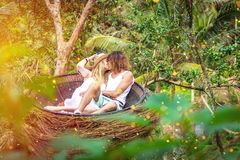 Man and Woman Kissing While Sitting in Round Brown Nest stock image