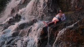 Man and woman kissing under the waterfall during sunset. The girl lies on the guy and kisses him, shooting under a waterfall among the rocks during sunset stock video footage
