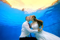 Man and woman kissing underwater in the swimming pool. Happy men and women in wedding dresses kissing underwater in the swimming pool on the background of a Stock Photo