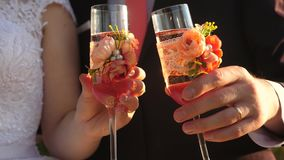 A man and a woman are knocking wine glasses with sparkling wine. Romantic meeting loving hearts. Close-up. A man and a woman are knocking wine glasses with stock video footage