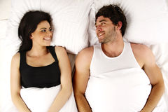 Man and woman laid in bed smiling to each other Stock Images
