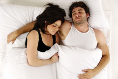 Man and woman laid in white bed asleep cuddling Royalty Free Stock Images