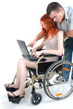 Man and woman with laptop on wheelchair Royalty Free Stock Photo