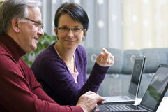 Man and woman with laptops. Man and a woman sit side by side on two laptop computers Stock Image