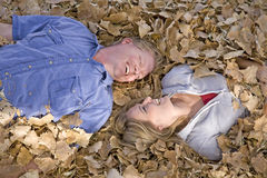 Man and woman in leaves close Stock Photos