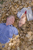 Man and woman in leaves looking at eachother Stock Photos