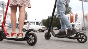 Man and woman legs ride future technology electric scooters