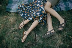 Man and woman lie in the summer on the grass close up. A man and a woman are lying on the grass in the summertime close up. A couple is lying on the grass stock photography
