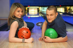 Man and woman liewith balls for bowling. Man and women lie on parquet leaning against an elbow and everybody holds ball for bowling, focus on hands girl Royalty Free Stock Images