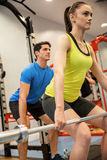 Man and woman lifting barbells together Stock Image
