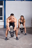 Man and woman lifting kettle bell crossfit Stock Images