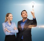 Man and woman with light bulb Stock Image