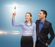 Man and woman with light bulb Stock Photos