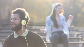 Man and woman listening to music on headphones and dancing to the rhythm stock video footage