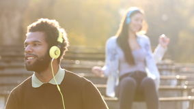 Man and woman listening to music on headphones and dancing to the rhythm stock video