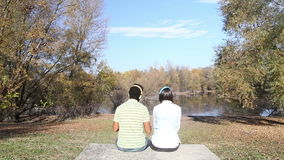 Man and woman listening to music using headphones while sitting by lake stock video footage