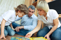 Man, woman and little boy reading book Royalty Free Stock Photo