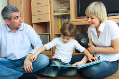 Man, woman and little boy reading book Royalty Free Stock Photography