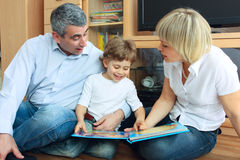 Man, woman and little boy reading book Royalty Free Stock Image