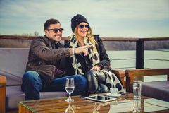 Man and woman loking at something and smiling. Man and women looking at something and smiling with river in background Royalty Free Stock Images
