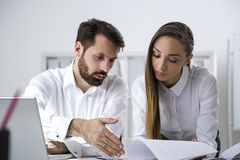 Man and woman with long hair reading report Royalty Free Stock Images