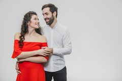 A man and a woman with long hair, supporting each other with love. Valentine`s Day. A woman dressed in a red dress of a. A men and a women with long hair royalty free stock photo